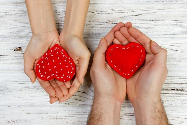 彼らの手に赤いハートを持って愛のカップル。バレンタインの日の概念