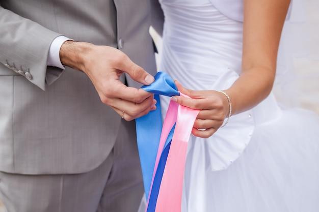 誕生のセックスをマークするためにピンクとブルーのリボンを保持している愛のカップル