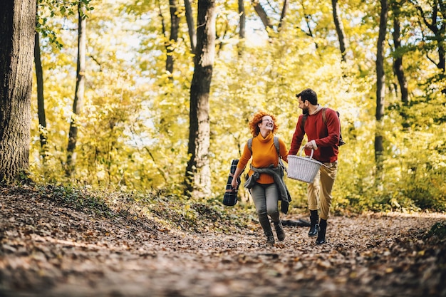美しい秋の日に手をつないで自然の中で走るのが大好きなカップル