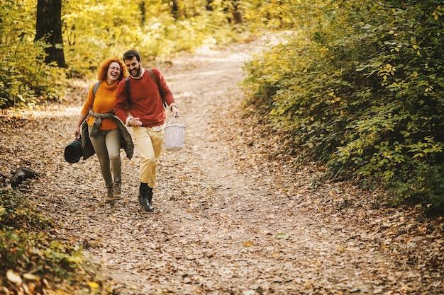 Влюбленная пара, взявшись за руки и гуляя на природе в прекрасный осенний день.