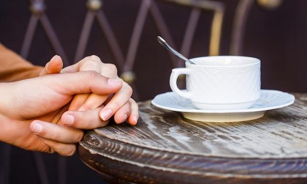 コーヒーと手をつないで恋にカップル。手をつないでいるカップル、ホットコーヒーのカップ。コーヒーを楽しむカップル。手にコーヒーのカップを保持している素敵なカップル。一杯のコーヒーを保持している女性と男性の手。