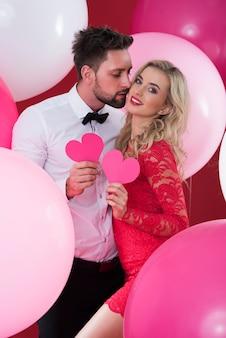 Влюбленная пара держит розовые сердечки из бумаги
