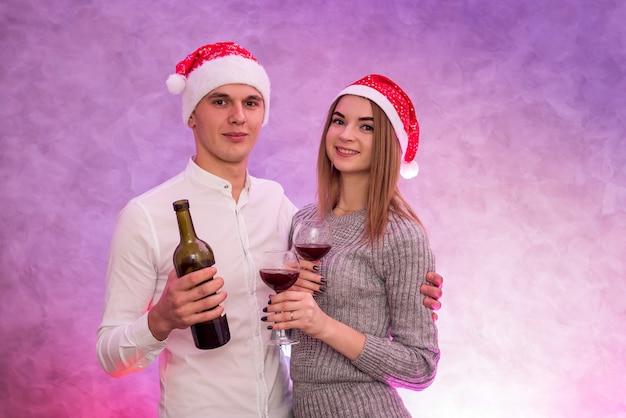 スタジオで聖バレンタインの日を祝うワインボトルとグラスを保持している愛のカップル