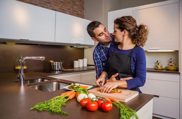 キッチンで健康的な野菜を抱き締めて準備するのが大好きなカップル。現代の家族のライフスタイルの概念。