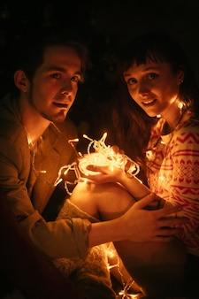 クリスマス前の夜に抱き締める恋のカップル。愛情のこもった抱擁、軽いクリスマスの花輪。男と女はお互いを愛しています。