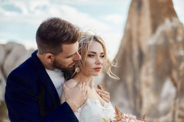 愛のカップルは、自然の中で素晴らしい山々で抱擁とキスをします。彼女の手に花束を持つ長い白いドレスの女の子、ジャケットの男。自然、人間関係、愛の中での結婚式