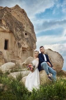 Влюбленная пара, объятия и поцелуи в сказочных горах на природе. девушка в длинном белом платье с букетом цветов в руках, мужчина в куртке