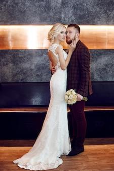 사랑에 빠진 커플은 결혼식 날에 포옹하고 키스합니다. 소식통 신랑과 신부, 사랑과 충성심. 이상적인 부부는 남편과 아내가되기 위해 준비하고 있습니다. 남자와여자가 서로보고 가까이