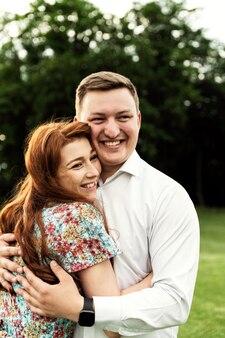 愛のカップルは日没時に自然の中で抱擁します。ロマンチックな設定。公園で妻と夫。恋人たちの散歩。若い家族の強い抱擁。