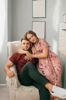 愛のカップルは明るい部屋と笑顔で家で一緒に抱擁します。