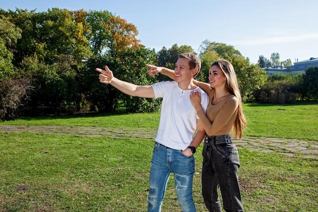 秋の公園で楽しんでいる良い気分で恋をしているカップル。公園の若いカップル
