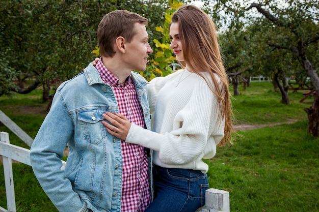 秋の公園で抱き締める良い気分で恋をしているカップル。公園の若いカップル