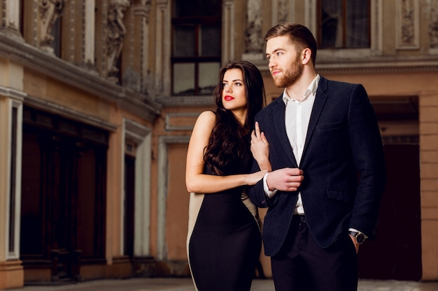 Пара в любви в элегантный наряд, прогулка по улице старого города. довольно брюнетка женщина с красными губами и ее красивый парень есть время отдыха.