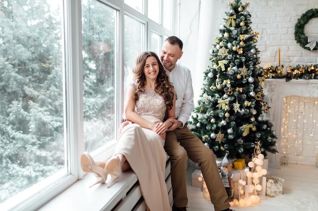 装飾されたスタジオの大きな窓とクリスマスツリーの近くに座って抱き締めるお祝いの服を着て恋をしているカップル。幸せな休日。