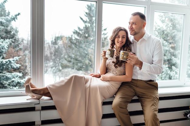 装飾されたスタジオの大きな窓とクリスマスツリーの近くに座って、抱き締めて、熱いお茶を飲んで、お祝いの服を着て恋をしているカップル。冬の幸せな休日。