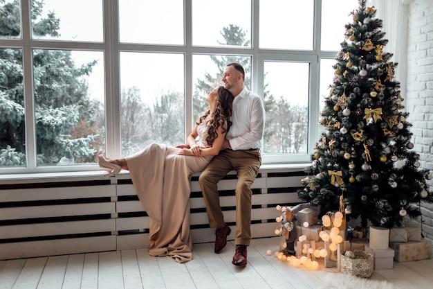 クリスマスツリーの近くに座っているお祝いの服を着て恋をしているカップル
