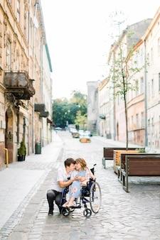 Пара в любви в старом центре города. молодая девушка с болезнью на инвалидной коляске и ее любимый мужчина