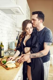 Влюбленная пара на кухне по утрам обнимает и готовит завтрак. счастливая семейная жизнь