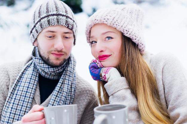 Влюбленная пара в теплой одежде сидит одна за другой на снегу и держит в руках чашки