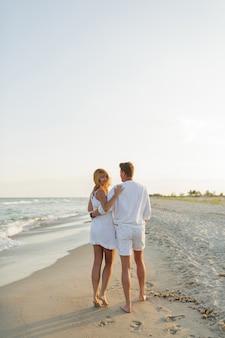ビーチを歩いている白い服を着た恋のカップル。完全な長さ。