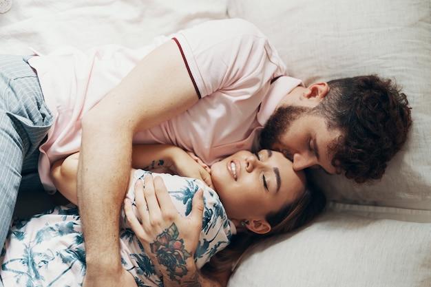 愛のカップルがベッドの上を受け入れています