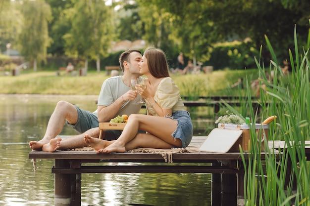 愛するカップルは、木製の桟橋の美しい場所で夏の日のピクニックにキスしています。幸福と静けさ。休息と楽しみ。人生の美しい瞬間。スーパーデイ。ロマンチックな関係。