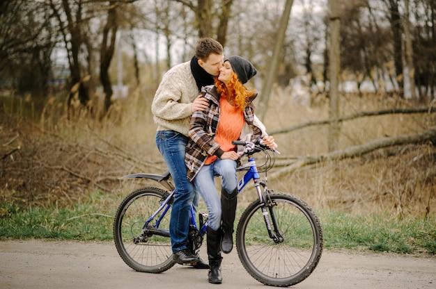 愛のカップルは公園で自転車に乗っています。