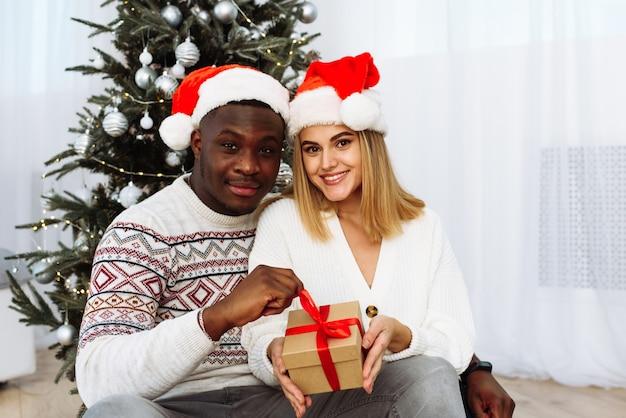 Влюбленная пара сидит в праздничной гостиной, украшенной рождеством, и держит подарок. оба счастливо смотрят прямо в камеру. веселого рождества и счастливого нового года