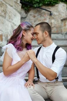 愛するカップルが階段に座って抱きしめています。男性と女性の間の愛と関係