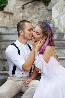 恋するカップルが階段に座って抱き合っている。男性と女性の愛と関係