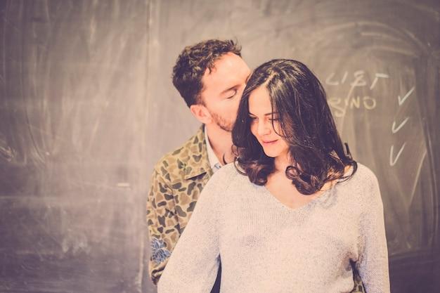 恋のカップルは、バック グラウンドで黒のラベルと自宅で優しさとキス