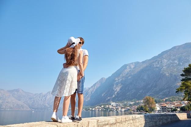 Влюбленная пара целуется на фоне морского побережья, гор и голубого неба