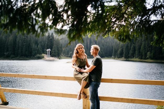 山々の自然旅行にキスする愛のカップル