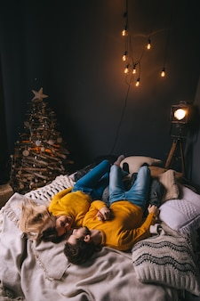 Влюбленная пара лежит на кровати и хочет поцеловать гирлянды на стене и елку