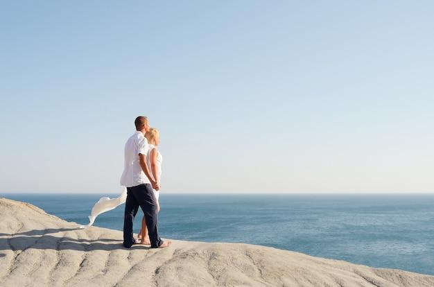 Влюбленная пара, глядя на море, взявшись за руки
