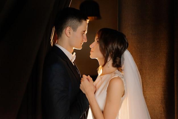 Влюбленная пара выглядит один на один. молодожены держатся за руки, глядя друг на друга в день свадьбы. низкий ключ.