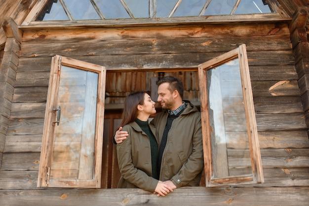 愛のカップルは窓、木造住宅の外に見えます。若い家族のために新しい住宅を購入するという概念。