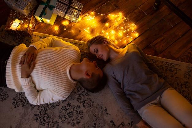 自宅の床に横になっている愛のカップル