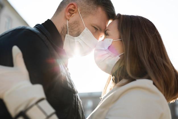 愛、男と女の顔に医療用保護マスクでお互いにキスのカップル。男、パンデミックコロナウイルス、ウイルス保護に対する少女。 covid19