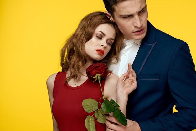 Влюбленная пара мужчина и женщина с красной розой классический костюм красное платье модель.