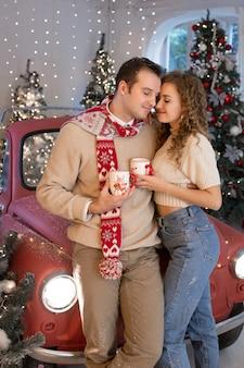 クリスマスの魔法を楽しんで、素敵に装飾されたクリスマスツリーの近くで恋をしているカップル。