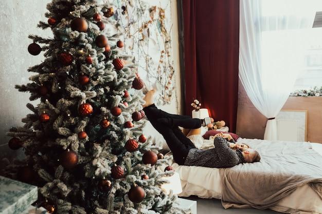 Влюбленная пара возле елки, лежа на кровати