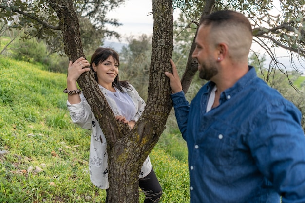木の隣で恋をしているカップル。きれいな女性に選択的に焦点を当てる
