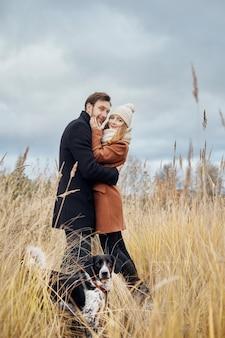 暖かい秋の日に恋をしているカップルは、陽気な犬のスパニエルと一緒に公園を散歩します。男性と女性の間の愛と優しさ。すべての愛好家のためのバレンタインデーの休日