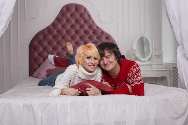 笑って楽しんでいる自宅のベッドで恋をしているカップル。デートを受け入れる若いカップルのデート