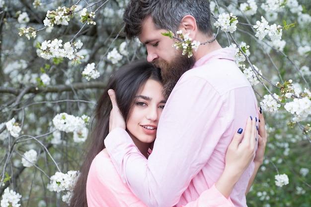 咲く木の近くの春のデートで恋をしているカップル。男と女は春の日に咲く庭で抱擁
