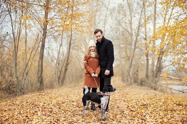발렌타인 데이에 사랑에 빠진 커플은 강아지와 함께 공원을 산책합니다. 남자와 여자 사이의 사랑과 부드러움. 발렌타인 데이는 모든 연인의 휴일입니다