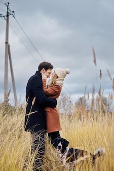 발렌타인 데이에 사랑에 빠진 커플은 강아지와 함께 공원을 산책합니다. 남자와 여자 사이의 사랑과 부드러움. 발렌타인 데이는 모든 연인의 휴일입니다.