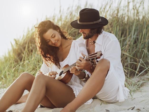 ギターを弾き、ビーチで休むのが大好きなカップル