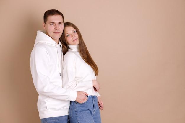 コピースペースで茶色の壁にポーズをとって恋のカップル